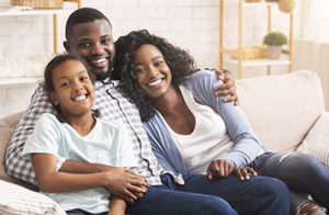 About Lovett Dental Beaumont, family of three sitting on couch smiling