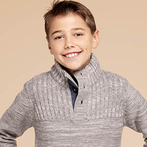 boy with grey sweater smiling