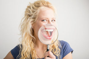 Teeth Whitening Services Beaumont Texas, woman holding magnifying glass over smile